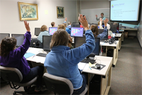 classroom computers and desks with students sitting raising on hand to the teach for an answer